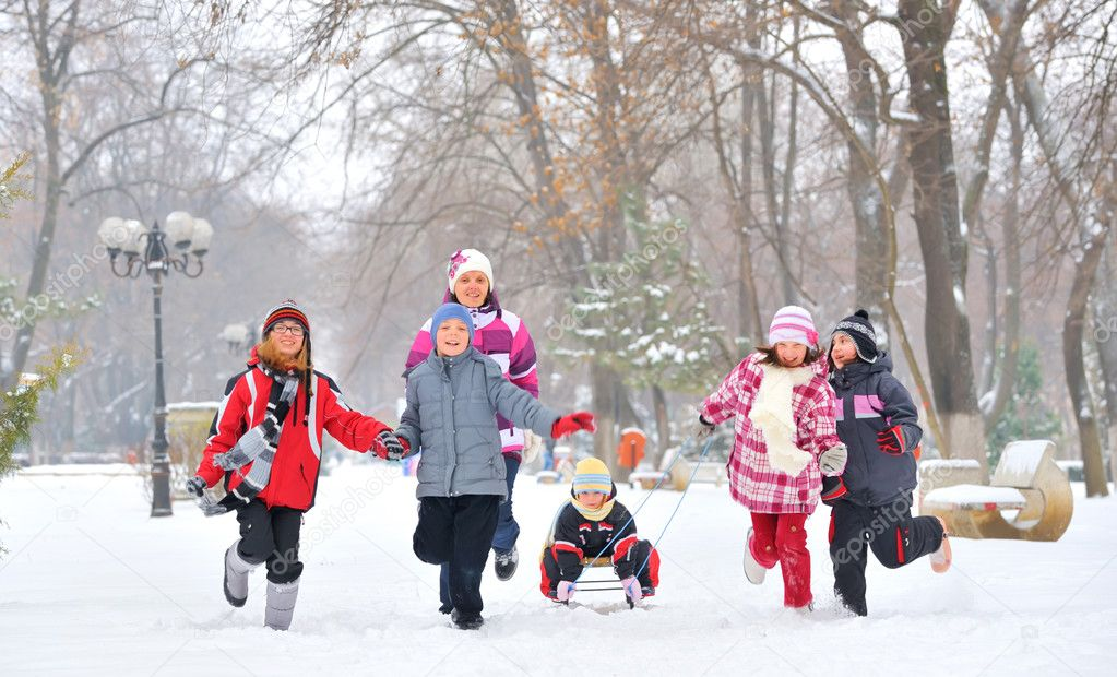 Group of children and mother playing on snow in winter time