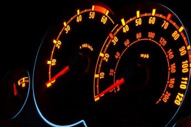 Backlit car dashboard dials glowing at night