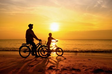 Father and son cycle ride on the beach in the sun rise