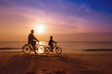 Father and son at the beach on sunset,Biker family silhouette