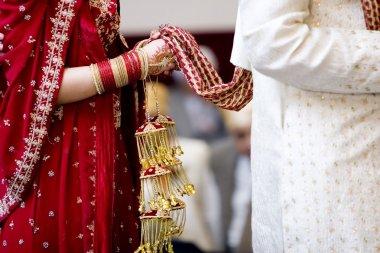 Hindu bride walks behind husband holding garb stock vector