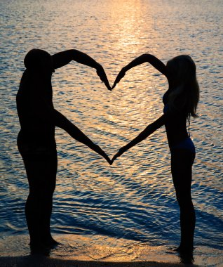 young couple making shape of heart with arms on beach against su