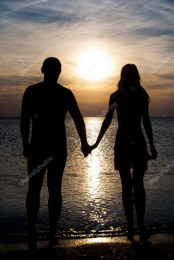 Young couple silhouette on a sea beach holding hands and lookin