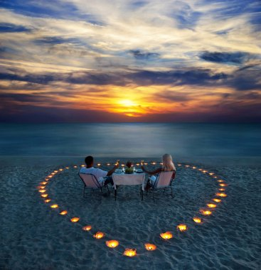 A young couple share a romantic dinner with candles heart on the sea sand beach stock vector