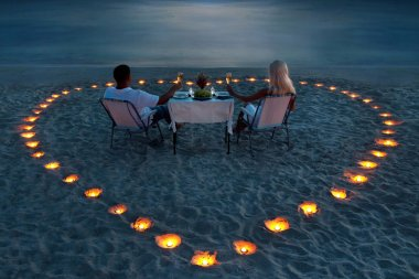 A young couple share a romantic dinner on the beach