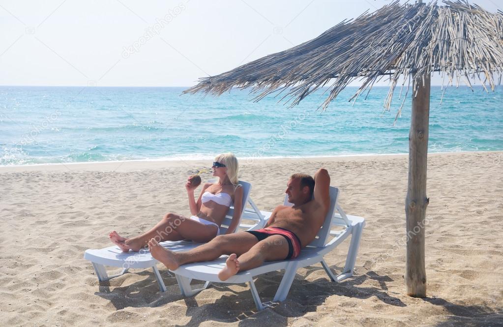 Sole Sotto L Ombrellone.Giovane Coppia Prendere Il Sole In Longue Sulla Spiaggia