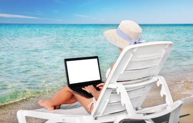 Cute woman with laptop in lounge on summer beach