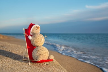 Sandy snowman sunbathing in beach lounge. Holiday concept for Ne