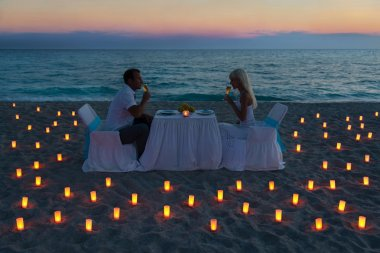 Lovers couple share a romantic dinner on sea beach