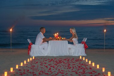 Young couple share a romantic dinner with candles