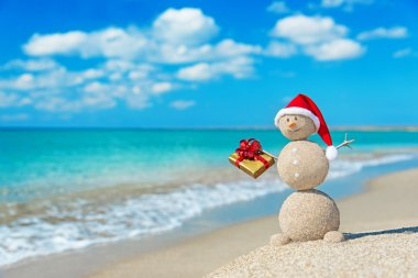 Smiley sandy snowman at beach in christmas hat
