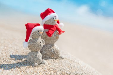 Snowmans couple at sea beach in christmas hat.