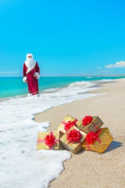 Santa Claus with many golden gifts relaxing on sea beach - chris