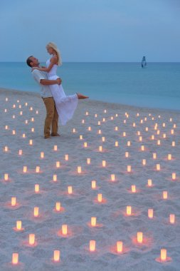 Proposal at sea beach in candles against sunset