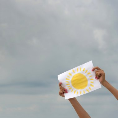 Sheet of paper with sun image against overcast sky