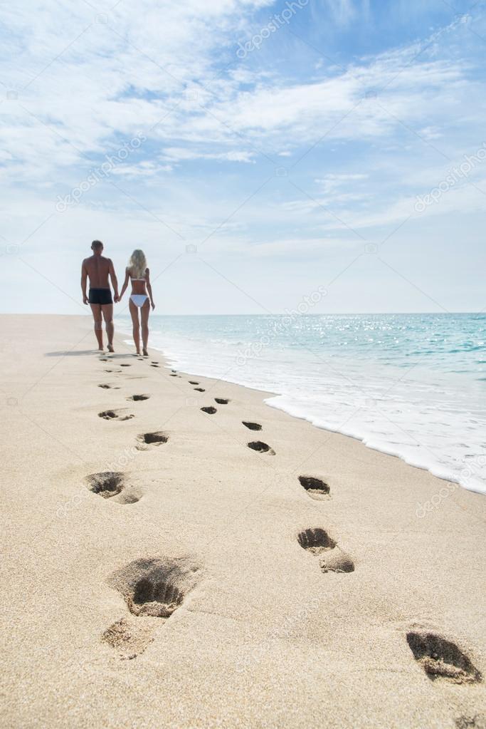 Loving couple walking with footprints at sea sandy beach