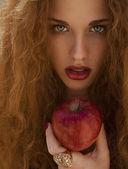 Fotografie Rote Leidenschaft. Frau mit einem Apfel