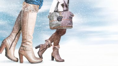 Female feet in winter shoes, snowfall in the foreground