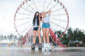 dvě mladé ženy smyslné bruslení v parku