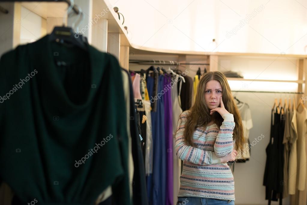 Woman shopping choosing dresses looking in mirror uncertain