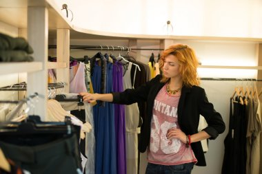 Woman shopping choosing dresses looking in mirror uncertain