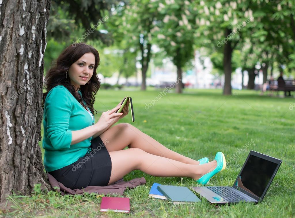 Mixed race college student lying down on the grass working