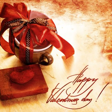 Present cup with a red ribbon bow with heart for Valentine's day
