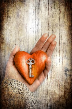 Heart with the key in women hand as a symbol of love