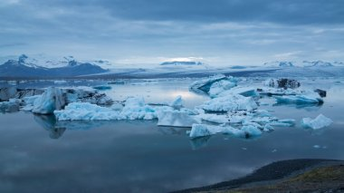 Blue icebergs floating under midnight sun