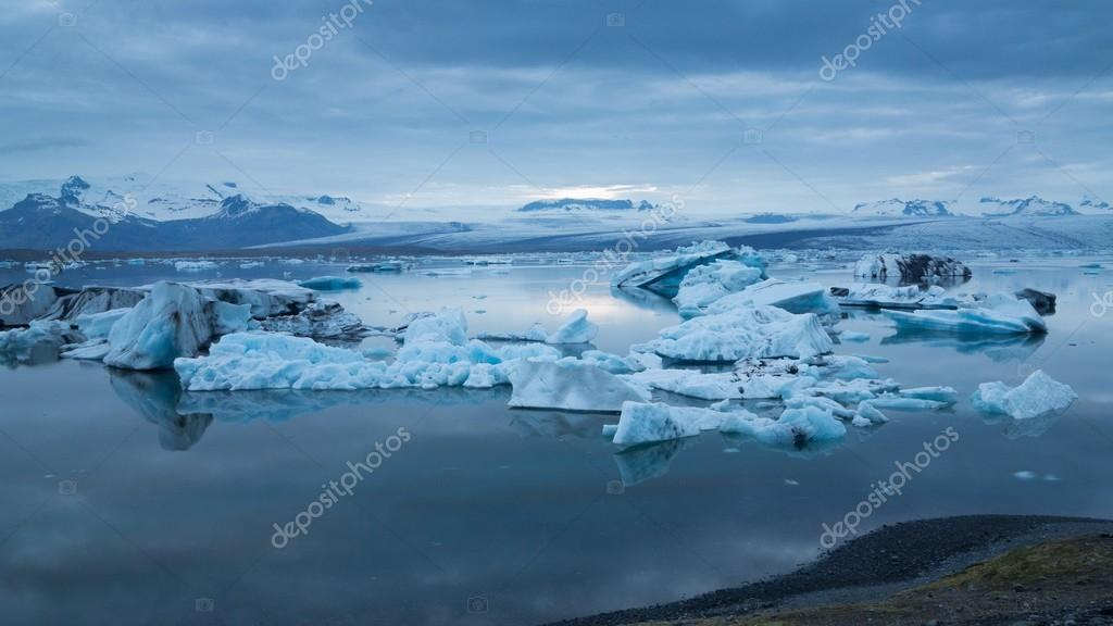Blue icebergs floating under midnight sun
