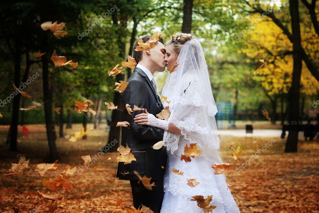 Newlyweds kissing in the autumn park