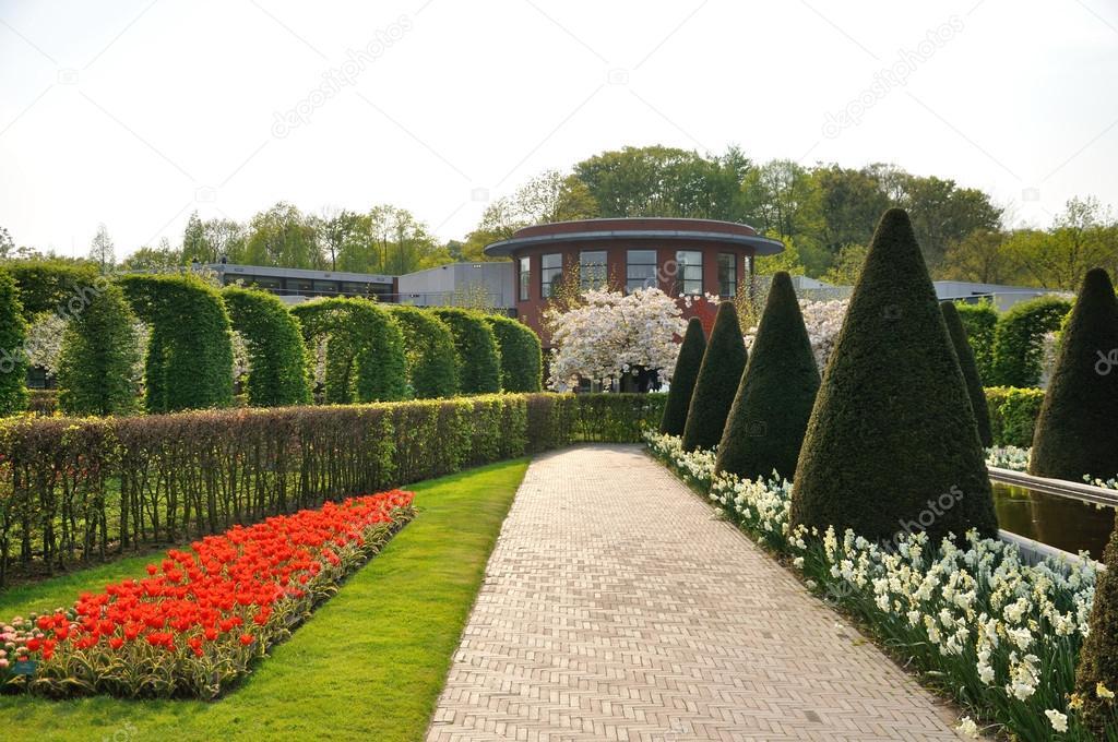 Garten mit Büschen, rote und weiße Blumen und Bäume im keukenhof ...