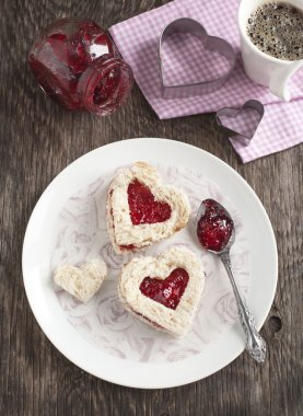 Heart shape sandwich with strawberry jam for breakfast