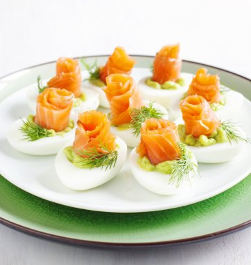 Stuffed eggs. Hard boiled eggs with avocado filling and smoked salmon