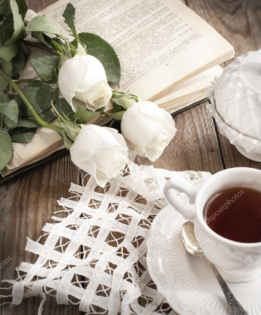 Cup of tea, books and roses on wooden table