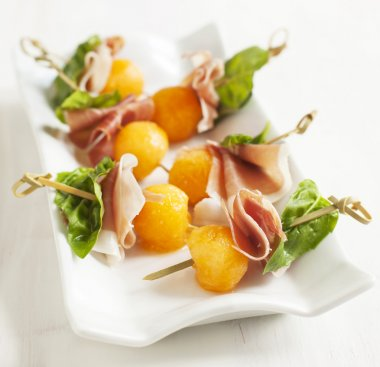 Appetizer with melon and prosciutto on skewers