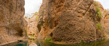 Panoramic photo at the bottom of the canyon of the Guadalevin river. Water mine of the House of the Moorish King. Casa dl Rey Moro. Spanish city Ronda. Malaga. Andalusia.