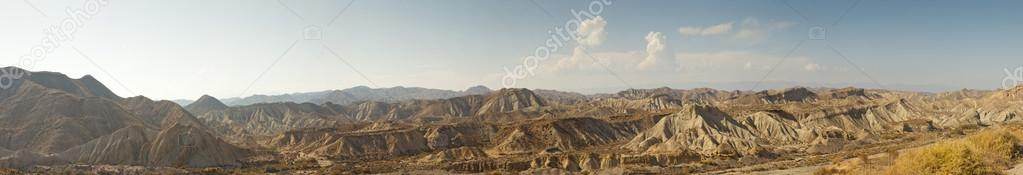 Panoramic photo of stunning desert landscape with mountains and blue sky. Desierto de Tabernas, Almeria. Andalusia. Spain.