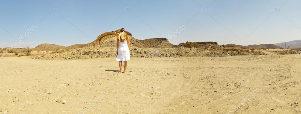 Panoramic photo of brunette female with white dress and hat standing in western landscape with stone arch. Fort Bravo. Texas Hollywood. Desierto de Tabernas, Almeria. Andalusia. Spain.