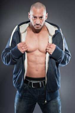 Muscled fitness man. Cool looking. Tough guy. Brown eyes. Bald. Wearing blue hoody shirt. Tanned skin. Studio shot isolated on grey background.