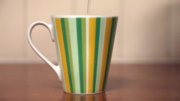 náplň barevná pohár s čaj stojící na dřevěný stůl v kuchyni