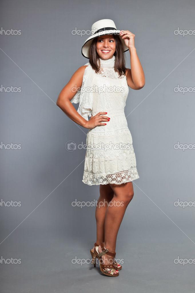 30da64b9a397a5 Mooi meisje met bruin haar en huid dragen witte jurk en hoed. expressie.  Knap. chique slijtage. studio portret geïsoleerd op grijze achtergrond —  Foto van ...