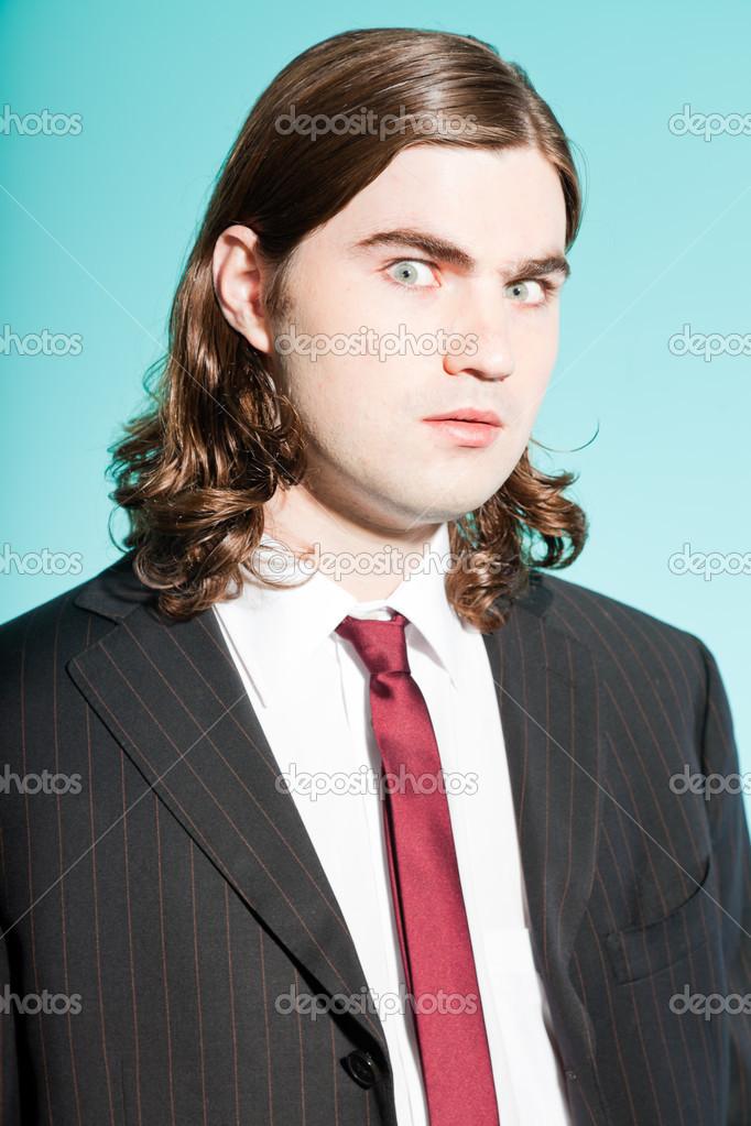Hombre de negocios enojado con pelo largo y castaño. vistiendo traje negro  a rayas y corbata roja oscura. tipo de pie — Foto de ysbrand 839b0b5539a