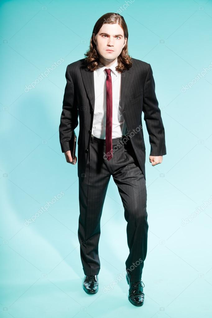 Hombre de negocios frustrados enojado con largo cabello castaño con  tableta. vistiendo traje negro a rayas y corbata roja oscura. tipo de pie —  Foto de ... e2308a3c051