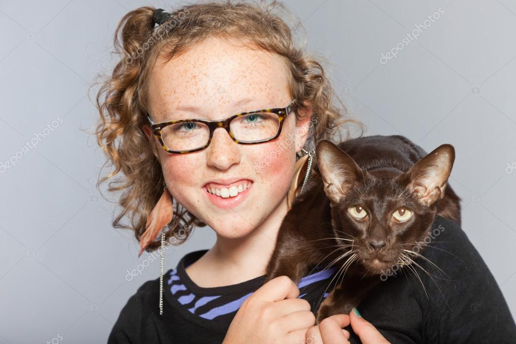 Happy teenage girl with glasses and blond curly hair hugging dark brown oriental shorthait cat.