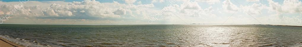 Beautiful panoramic shot of dutch Wadden sea with blue stormy cloudy sky.