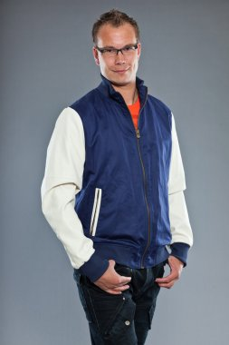 Happy young man with short hair wearing blue baseball jacket and blue jeans. Wearing black glasses. Sportive casual look. Studio shot isolated on grey background. stock vector