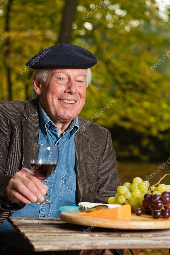 Senior french man enjoying red wine.
