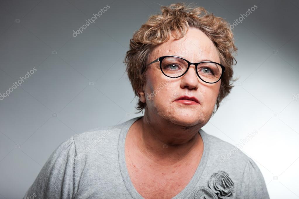 Senior Mujer Con Pelo Corto Rizado Studio Disparo Contra El Fondo - Pelo-corto-rizado-mujer
