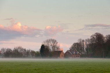 Meadow with house in the mist at sunset. Cloudy sky. Spring time. City skyline.